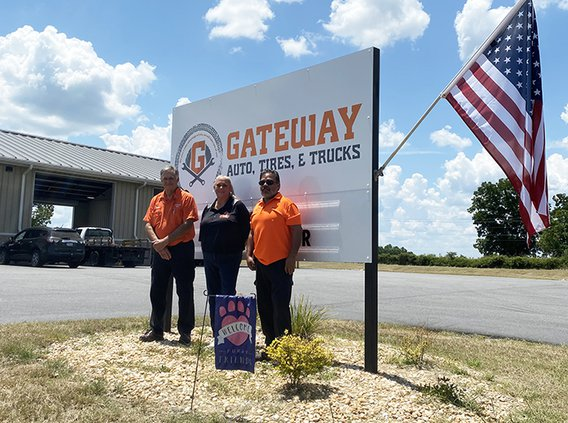 Tabatha Anderson, center, stands with Ricky Pearson, left, and Ricky Espinoza at at Gateway Auto, Tires & Trucks.