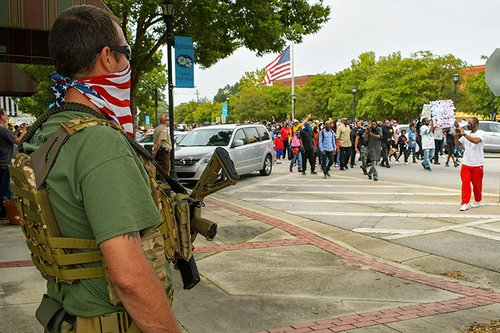 An armed bystander watches protesters march by in downtown Sylvania during the Justice Caravan for Julian Lewis on Saturday.