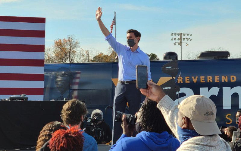 Georgia Democrat Jon Ossoff waves to the crowd at a rally to boost his U.S. Senate campaign, appearing along with Raphael Warnock and hip-hop artist Common, in Garden City on Dec. 19.