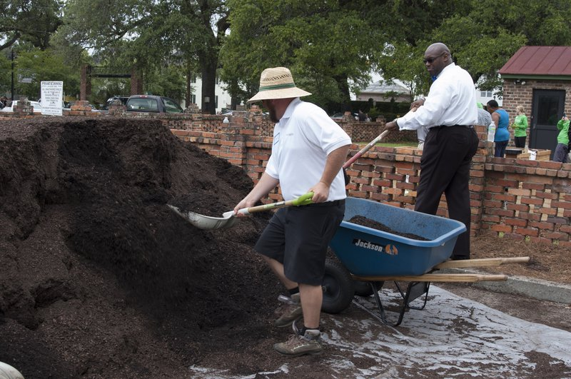 Victory Gardens' David Hislop moves soil to the raised garden beds with the help of C. MeGill Brown, pastor of Second African Baptist Church, Savannah Police Department Chaplain, and president of Curtis V. Cooper Primary Health Care's Board of Directors.