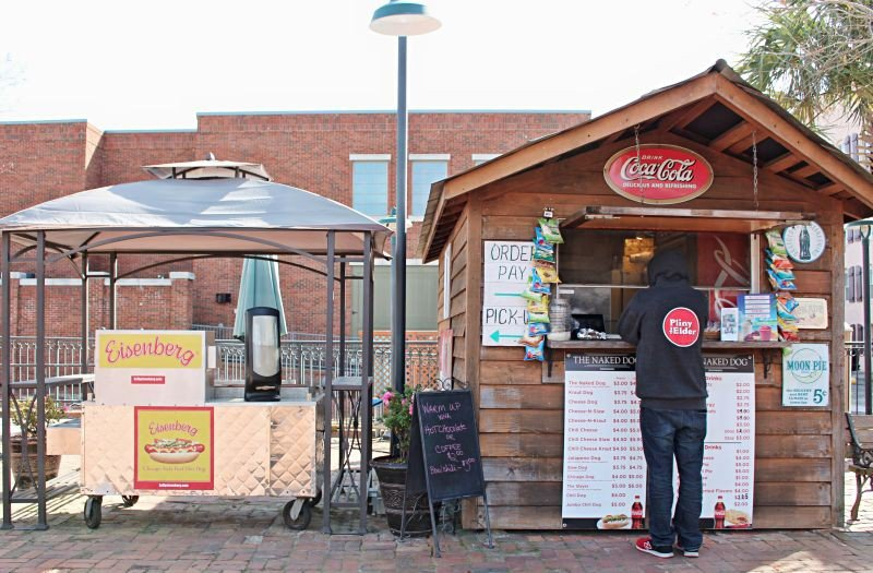 The Naked Dog, on River Street, is housed in a traditional hotdog cart sandwiched between two wooden sheds that offer Repicci's Italian Ice, drinks and snacks.
