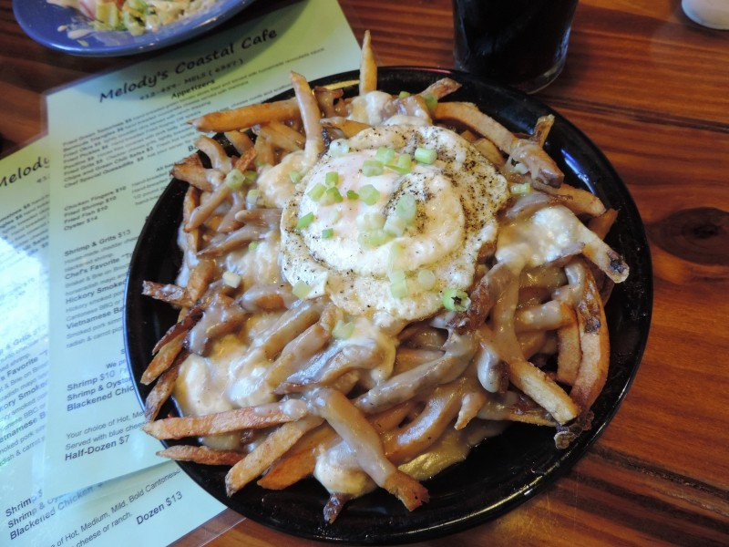 French-Canadian Poutine: hand-cut fries, topped with light gravy, fried pork belly, cheese curds,    a fried egg & scallions--listed as an appetizer but definitely a meal!