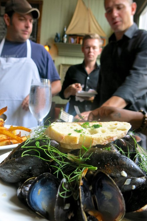 Chef David Landrigan, left, and company enjoy some of their kitchen's handiwork, in this case the amazing mussels.