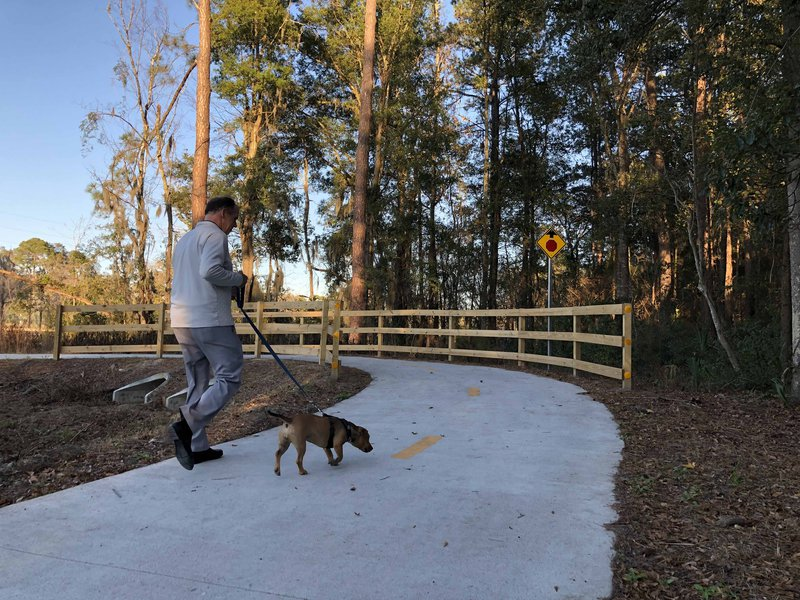 A man walks his dog on the newly completed Truman Linear Park Trail.