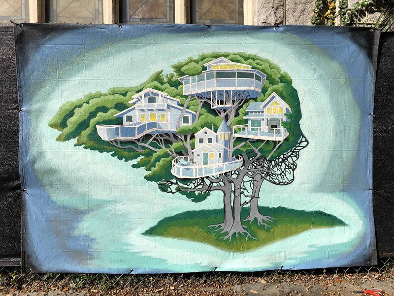 A Fence Art Project mural by Brian MacGregor hangs in front of a Starland Village construction site.