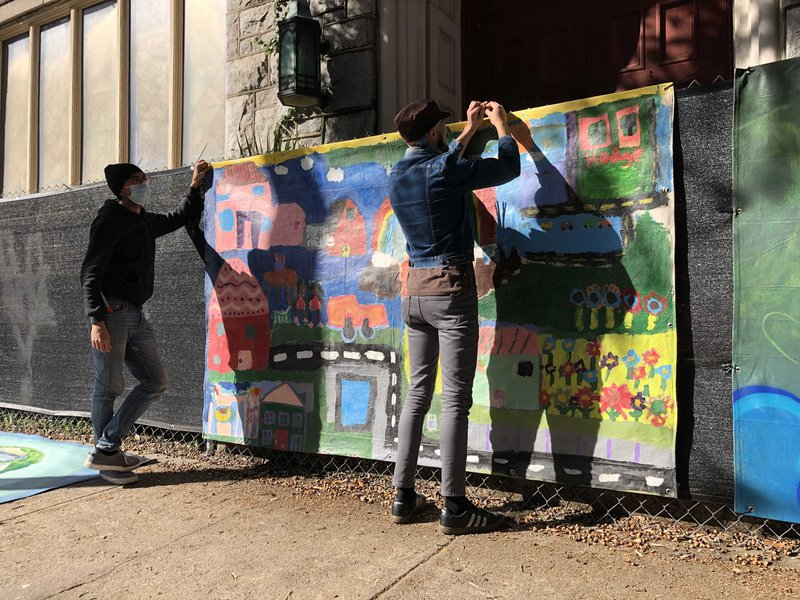 Clinton Edminster (left) and José Ray hang Fence Art Project murals at Starland Village.