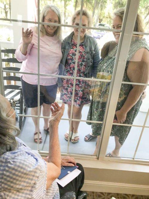 Emily Calhoun visiting her mom through a window.