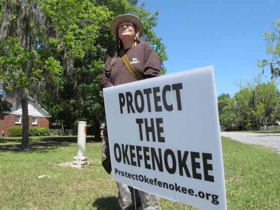 """Jane Winkler stands with a sign that says """"Protect The Okefenokee"""" outside a church where Georgia Gov. Brian Kemp met with local Chamber of Commerce members in Folkston, Ga., on April 22, 2021. Winkler and others are fighting a mining company's plan to di"""