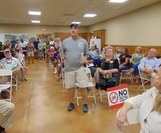 """Brooklet residents Roger Wentz, standing to speak, and wife Sheila Wentz, seated with sign at her feet, are definitely in the """"no"""" camp on the current plan for the S&S Greenway Trail extension. But opponents and supporters were about evenly divided at the"""
