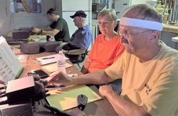 Two local teams of two persons each have one ham radio operator call other stations while the other keeps the contact log in this photo from the 2019 Amateur Radio Field Day. The individuals are, from left background to right front:  John Smoyer III, call