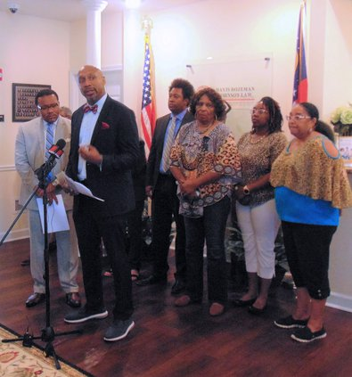 AL HACKLE/staff Attorney Mawuli Davis, behind microphone, talks about what he,  law partner Francys Johnson,  left, and members of the family of the late Julian Lewis, behind them, saw in evidence shown by the district attorney and voices demands for a ne