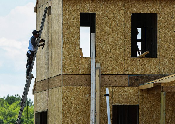 A worker helps construct a building at Keystone Homes at Chatham Place on Wednesday, June 23. Private developers are planning and developing residential subdivisions at a near-record pace in Bulloch County, while shortages and skyrocketing prices of build