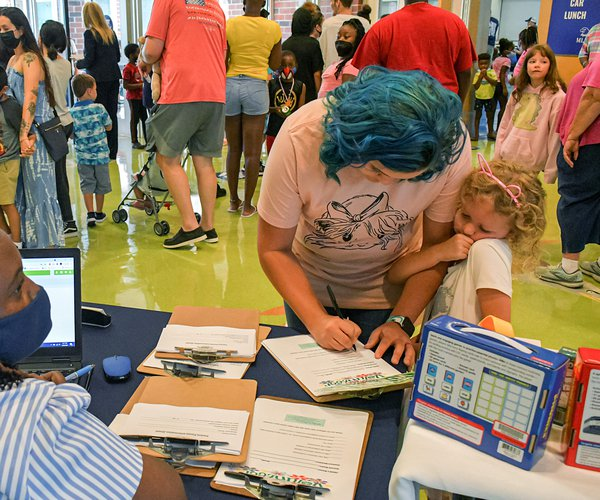 Kindergartener Harper Willis, 5, snuggles with mom Cheyenne as they check in with family engagement specialist Sharon Wilkins, left, during open house at Mattie Lively Elementary School on Thursday, July 29. All Bulloch County schools open the doors to we