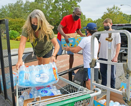 Statesboro Food Bank manager Jodi Brannon, left, hoists a case of water into a cart while James Harris hands off a box to volunteers from Georgia Southern as they unload donations from Walmart at the Statesboro Food Bank on Friday, Sept. 17.