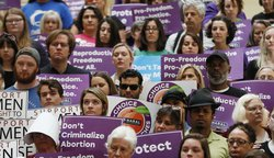 In this May 16, 2019 file photo, abortion rights supporters stand during a news conference by Presidential candidate Sen. Kirsten Gillibrand, D-N.Y., at the Georgia State Capitol in Atlanta to discuss abortion bans in Georgia and across the country. A fed