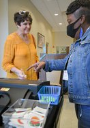 Poll worker Rhenetri Washington, right, helps Chris Van Tassell finish casting her ballot during early voting at the Bulloch County Annex on Friday, Oct. 15.