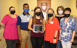 Erin Seidl stands with her Finance team after being awarded Employee of the Month this past week at EGRMC.